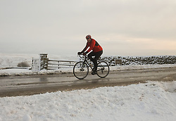 © Licensed to London News Pictures. <br /> 27/12/2014. <br /> <br /> Castleton, United Kingdom.<br /> <br /> A lone cyclist makes his way over one of the moor roads on the North Yorkshire Moors after overnight snowfall caused disruption in some parts of the country.<br /> <br /> Photo credit : Ian Forsyth/LNP
