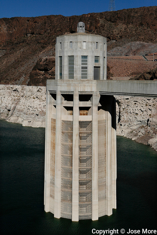 Large intake towers take water from lake Mead into the dam to create hydroelectric power. Dedicated on September 30, 1935, by President Franklin D. Roosevelt, the Hoover Dam, once known as Boulder Dam, is a concrete arch-gravity dam in the Black Canyon of the Colorado River, on the border between the U.S. states of Arizona and Nevada. It was constructed between 1931 and 1936 during the Great Depression. Its construction was the result of a massive effort involving thousands of workers, and cost over one hundred lives. The dam was named after President Herbert Hoover.<br /> Photography by Jose More