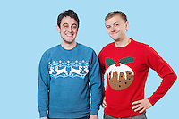Portrait of young men in warm clothing standing against blue background