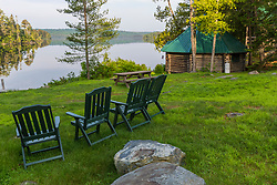 Adirondack Chairs and Cabin 8 next to Long Pond outside the Appalachian Mountain Club's Gorman Chairback Lodge.