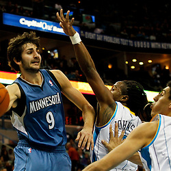 January 13, 2012; New Orleans, LA, USA; Minnesota Timberwolves point guard Ricky Rubio (9) passes as New Orleans Hornets guard Carldell Johnson (5) and power forward Gustavo Ayon (15) defend during the second half of a game at the New Orleans Arena. The Timberwolves defeated the Hornets 87-80.  Mandatory Credit: Derick E. Hingle-USA TODAY SPORTS