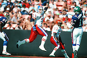Denver Broncos nose tackle Greg Kragen leaps while trying to knock down a pass thrown by Philadelphia Eagles quarterback Randall Cunningham (12) during the 1990 NFL Pro Bowl football game between the AFC American Football Conference and the NFC National Football Conference on Feb. 4, 1990 in Honolulu. The NFC won the game 27-21. (©Paul Anthony Spinelli)