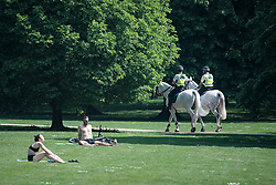 © Licensed to London News Pictures. 09/05/2020. London, UK. Mounted police patrol past people sunbathing in St James's Park, central London during lockdown. The government is set to announce measures to ease lockdown, which was introduced to fight the spread of the COVID-19 strain of coronavirus. Photo credit: Ben Cawthra/LNP