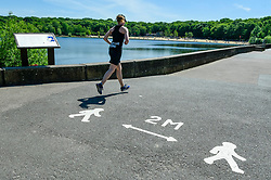 © Licensed to London News Pictures. 20/05/2020. LONDON, UK.  A runner passes a 2 metre distancing sign on the tarmac as members of the public take advantage of the easing of certain coronavirus pandemic lockdown restrictions to enjoy the sunshine and warm weather at Ruislip Lido in north west London.   The forecast is for temperatures to rise to 29C, the hottest day of the year so far.  Photo credit: Stephen Chung/LNP