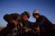 Mongolia. nomads smoking. cattle breeders in the steppe coming from the Gobi desert   / to oulan bator to sell their sheeps / nomade fumant une cogarette; cavaliers dans la steppe à l'ouest de Ulan Baatar en provenance du désert de Gobi . caravanne de chameaux. cavaliers dans la steppe à l'ouest de Ulan Baatar en provenance du désert de Gobi ces eleveurs du desert de Gobi cheminent depuis quatre mois pour rejoindre la capitale Oulan Bator ou ils vont  vendre leur troupeau Mongolie   / P0000607  D