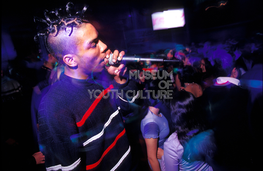 A teenager on the microphone at a club, Uk 1990's