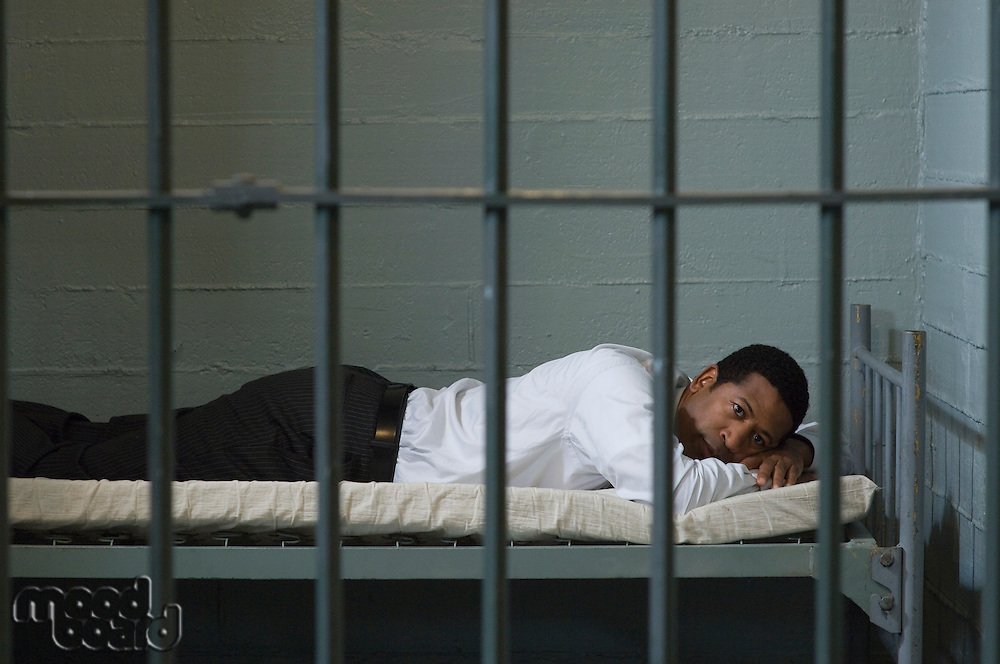 Man lying in prison cell