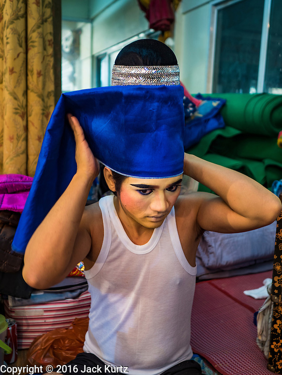 """30 JANUARY 2016 - NONTHABURI, NONTHABURI, THAILAND: A performer puts on his stylized hat before a """"likay"""" show at Wat Bua Khwan in Nonthaburi, north of Bangkok. Likay is a form of popular folk theatre that includes exposition, singing and dancing in Thailand. It uses a combination of extravagant costumes and minimally equipped stages. Intentionally vague storylines means performances rely on actors' skills of improvisation. Like better the known Chinese Opera, which it resembles, Likay is performed mostly at temple fairs and privately sponsored events, especially in rural areas. Likay operas are televised and there is a market for bootleg likay videos and live performance of likay is becoming more rare.     PHOTO BY JACK KURTZ"""