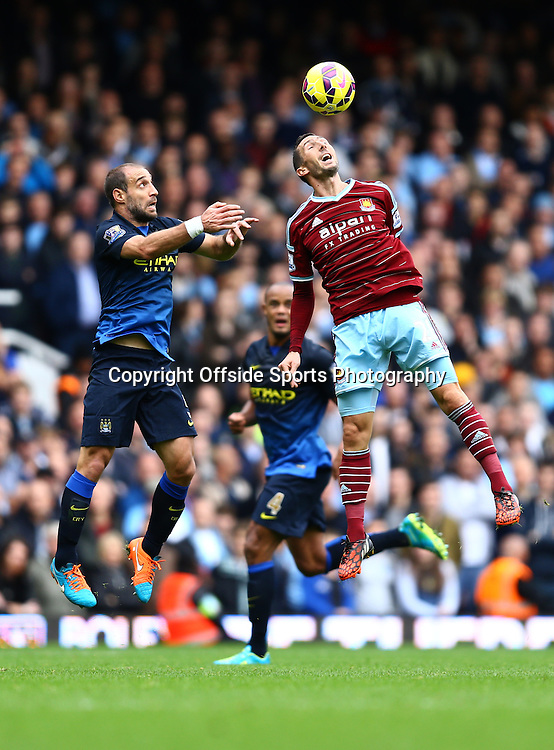 25 October 2014 - Barclays Premier League - West Ham v Manchester City - Pablo Zabaleta of Manchester City challenges for a high ball with Morgan Amalfitano of West Ham - Photo: Marc Atkins / Offside.