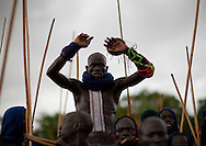 "Fighters arrive on the Donga field all together, carrying the strongest man while dancing and singing ""I'm the hero, who's gonna fight me?"".  One of the main Surma / Suri customs is stick fighting. This ritual and sport is called Donga or Sagenai (Saginay). Donga is both the name of the sport and the stick, whereas sagenai is the name of the stick-fighting session. Stick fighting is basic in Suri culture. In most cases, stick fighting is a way for warriors to find girlfriends, it can also be a way to settle conflicts. On this occasion men  show their courage, their virility and their resistance to pain, to the young women. The fights are held between Suri villages, and begin with 20 to 30 people on each side, and can end up with hundreds of warriors involved."