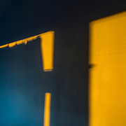 Evening shadows and reflections of a curtain on a yellow wall
