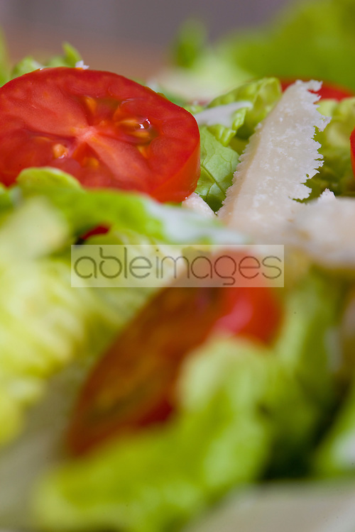 Extreme close up of a mixed salad with tomatoes and parmesan shavings