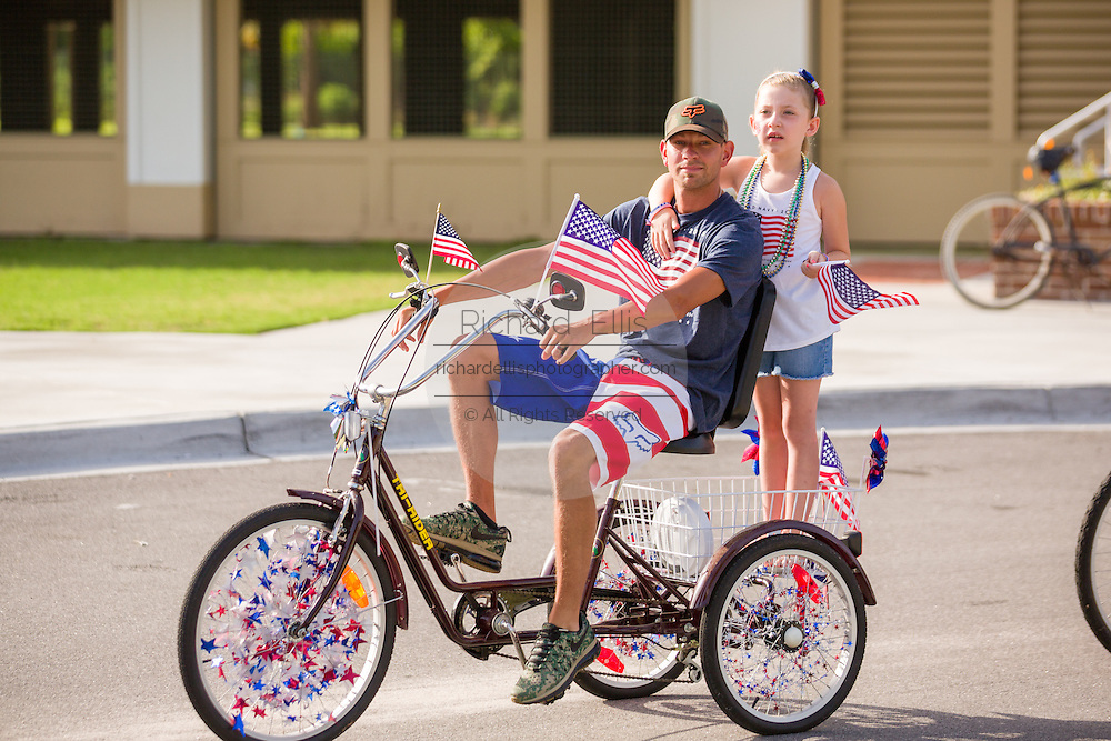 A father and daughter ride past on a tricycle decorated with bunting and American flags during the Sullivan's Island Independence Day parade July 4, 2015 in Sullivan's Island, South Carolina.