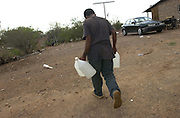 An undocumented migrant fills water jugs at a home about 25 miles north of the Mexican border on the Tohono O'odham Reservation, Arizona, USA.