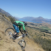 Jon Stout, UK, in action during the New Zealand South Island Downhill Cup Mountain Bike series held on The Remarkables face with a stunning backdrop of the Wakatipu Basin. 150 riders took part in the two day event. Queenstown, Otago, New Zealand. 9th January 2012. Photo Tim Clayton