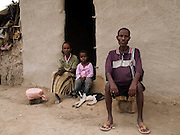 Shekur Mohammaed, 60 and his wife, Fatuma Delbo, 40, with one of their daughters Elefelesh, 9 years old outside their house in Zwei, Ethiopia...Shekur and his family are beginning to really suffer as their maize crops have failed due to a lack of rain. SEDA, who work with Send a Cow, are about to start work with them to teach them some basic farming techniques to diversify their crop range and improve their yield, even when the rains don't come...The first step is under way and Shekur has paid a specialist well digger to start digging a well.