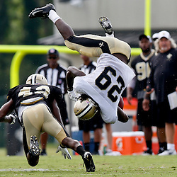 Aug 3, 2013; Metairie, LA, USA; New Orleans Saints free safety Isa Abdul-Quddus (42) hits running back Khiry Robinson (29) flipping him into the air during a scrimmage at the team training facility. Mandatory Credit: Derick E. Hingle-USA TODAY Sports