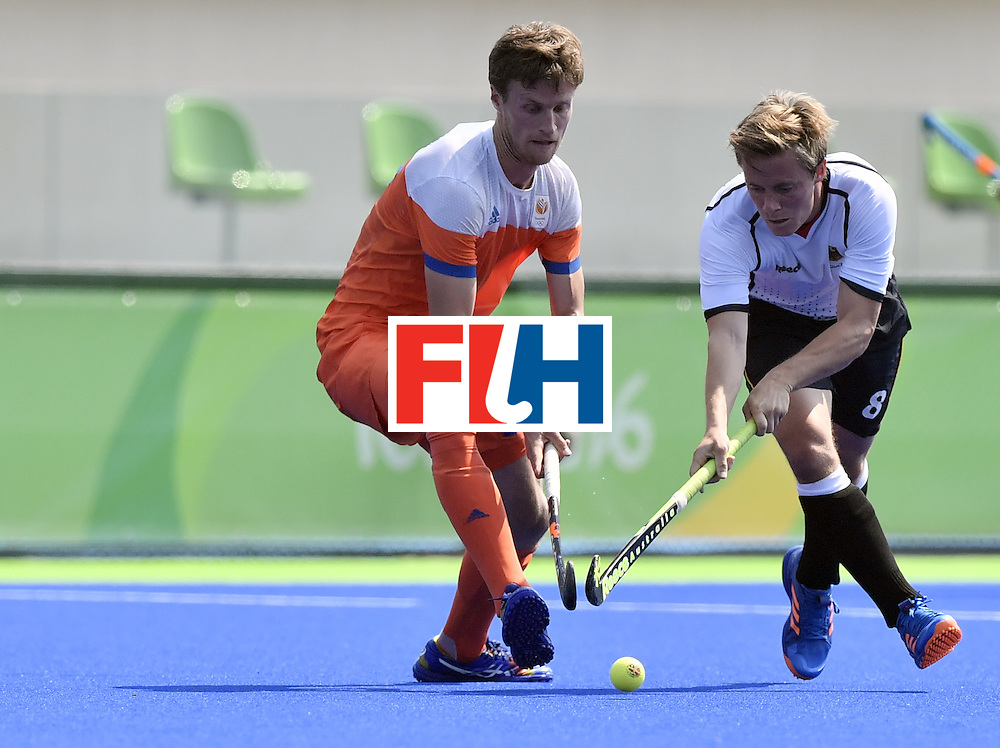 Germany's Mats Grambusch vies with Netherlands' Hidde Turkstra (L) during the men's Bronze medal field hockey Netherlands vs Germany match of the Rio 2016 Olympics Games at the Olympic Hockey Centre in Rio de Janeiro on August 18, 2016. / AFP / PHILIPPE LOPEZ        (Photo credit should read PHILIPPE LOPEZ/AFP/Getty Images)