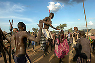 Mundari herdsmen celebrate the slaughtering of a cow at a cattle camp in Central Equatoria Province. The tribe suffered from inter-tribal conflicts and cattle rustling in the northern part of the province forcing them to move further south in search of safer grazing land. Thousands have been killed and hundreds of thousands displaced by inter-tribal violence, exacerbated by climae change induced draught and political rivalry.<br /> Kuruki, South Sudan. 12/10/2009.