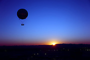 A hot air balloon silhouetted in the sky as the sun rises behind the desert mountains.