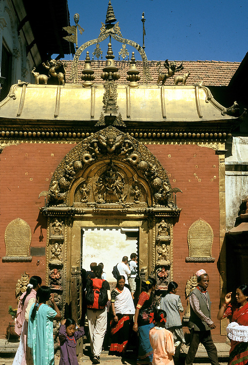 Bhaktapur, World Heritage city, Golden Gate (actually brass), built 1785 as entrance to royal palace.  Group of 8-12 men and women cluster around the gate to enter the palace within..