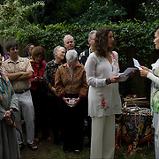 Leigh and Helena reading, pledging their commitment vows to each other at the Sacred Union  Celebration in the back yard of friends