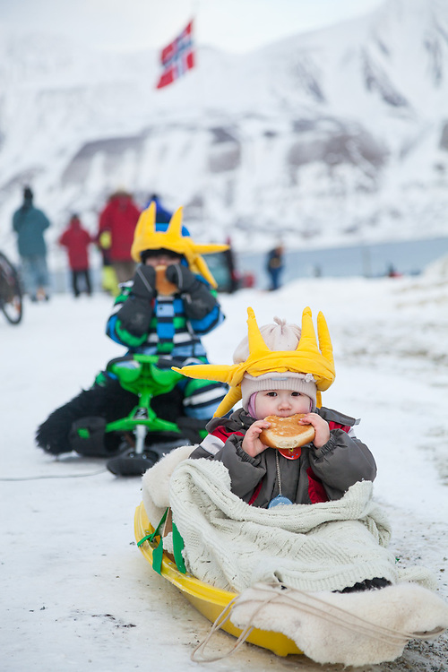 Children, pulled in sleds, eat their sun buns (solboller) at SolFest in Longyearbyen, Svalbard. The festival marks the official arrival of the sun to the town – by tradition, to the old hospital steps (sykehustrappa).