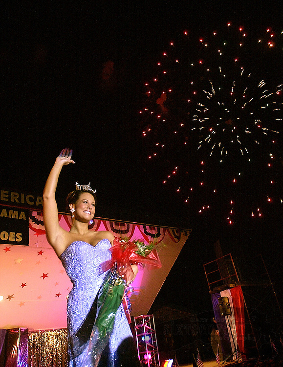 Photo by Gary Cosby Jr.  Jessica Wheeler celebrates her victory in the Miss Point Mallard contest as fireworks burst overhead in celebration of the Fourth of July in Point Mallard Park, Decatur, Alabama.