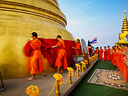 15 NOVEMBER 2018 - BANGKOK, THAILAND: Monks wrap the chedi at the top of Wat Saket, also called the Golden Mount, during the red cloth ceremony. Wat Saket is on a man-made hill in the historic section of Bangkok. The temple has golden spire that is 260 feet high, which was the highest point in Bangkok for more than 100 years. The temple construction began in the 1800s during the reign of King Rama III and was completed in the reign of King Rama IV. A  red cloth (reminiscent of a monk's robe) is placed around the chedi at the top of  Golden Mount during the weeks leading up to the Thai holy day of Loy Krathong, which is November 22 this year.     PHOTO BY JACK KURTZ
