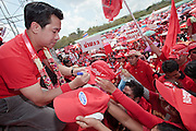 """Mar. 26, 2009 -- BANGKOK, THAILAND: JAKRAPOB PENKAIR, former spokesman for ousted Thai Prime Minister Thaksin Shinawatra signs autographs during an anti-government rally in Bangkok Thursday. More than 30,000 members of the United Front of Democracy Against Dictatorship (UDD), also known as the """"Red Shirts""""  and their supporters descended on central Bangkok Thursday to protest against and demand the resignation of current Thai Prime Minister Abhisit Vejjajiva and his government. Abhisit was not at Government House Thursday. The protest is a continuation of protests the Red Shirts have been holding across Thailand in March.  Photo by Jack Kurtz"""