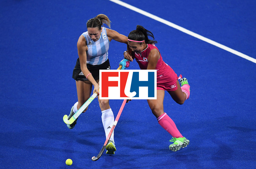 Japan's Aki Mitsuhashi (R) vies for the ball with Argentina's Victoria Zuloaga during the women's field hockey Argentina vs Japan match of the Rio 2016 Olympics Games at the Olympic Hockey Centre in Rio de7aneiro on August, 8 2016. / AFP / MANAN VATSYAYANA        (Photo credit should read MANAN VATSYAYANA/AFP/Getty Images)
