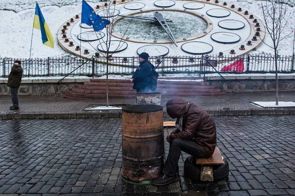 KIEV, UKRAINE - DECEMBER 7: An anti-government protester keeps warm by a fire on December 7, 2013 in Kiev, Ukraine. Thousands of people have been protesting against the government since a decision by Ukrainian president Viktor Yanukovych to suspend a trade and partnership agreement with the European Union in favor of incentives from Russia. (Photo by Brendan Hoffman/Getty Images) *** Local Caption ***