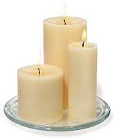 three varied size lit candles on glass dish