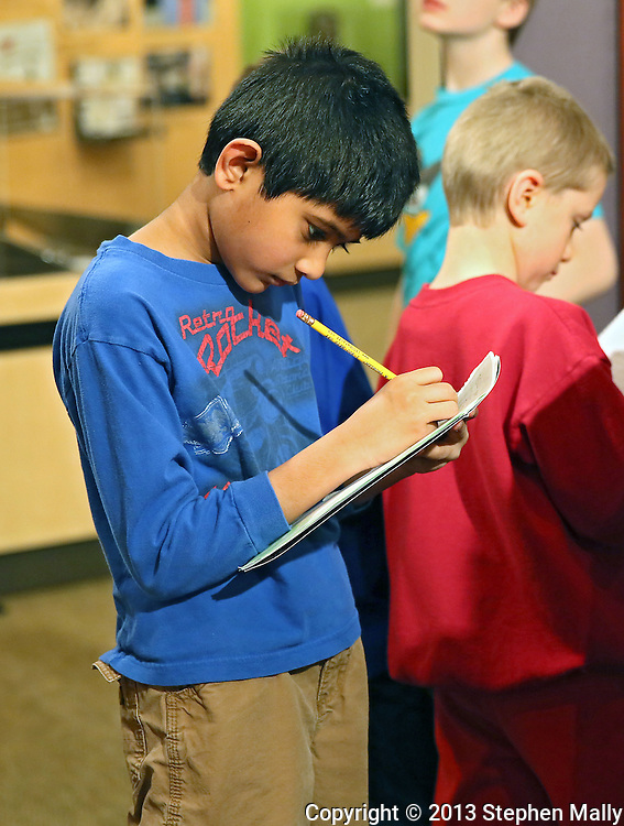 Arjun Palaniappan, 9, of Westfield Elementary School takes notes as he goes through at the African American Museum of Iowa in Cedar Rapids on Friday, March 22, 2013.