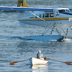 A float plane and a man in a canoe make their way through the water near Nanaimo, Canada.