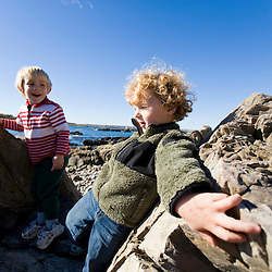 Two boys (age 4) play on a cobble beach in Biddeford, Maine. Timber Point.