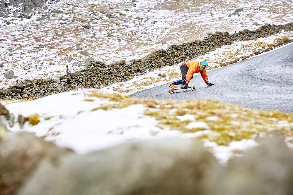 A photogrpah of a downhill skateboarder skating the Struggle during the beast from the east, near Kirkstone Pass in the Lake District, England.