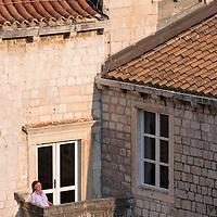 A man soaks in the sun from a balcony of the Dominican monastery. Scene in the UNESCO World Heritage Site of Dubrovnik's Old Town on the Dalmatian Coast in Croatia.