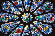East Rose window, stained glass by Jacques Bony, 1979-80, in the Collegiate Church of Saint-Gervais-Saint-Protais, built 12th to 16th centuries in Gothic and Renaissance styles, in Gisors, Eure, Haute-Normandie, France. The church was consecrated in 1119 by Calixtus II but the nave was rebuilt from 1160 after a fire. The church was listed as a historic monument in 1840. Picture by Manuel Cohen