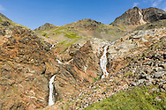 Waterfalls originating from snow melt in Crow Pass will combine to form Crow Creek in Chugach National Forest in Southcentral Alaska. Summer. Afternoon.