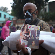 A egyptian protestor shows mock photographs of interim government leaders, during clashes with the security forces in central Cairo.