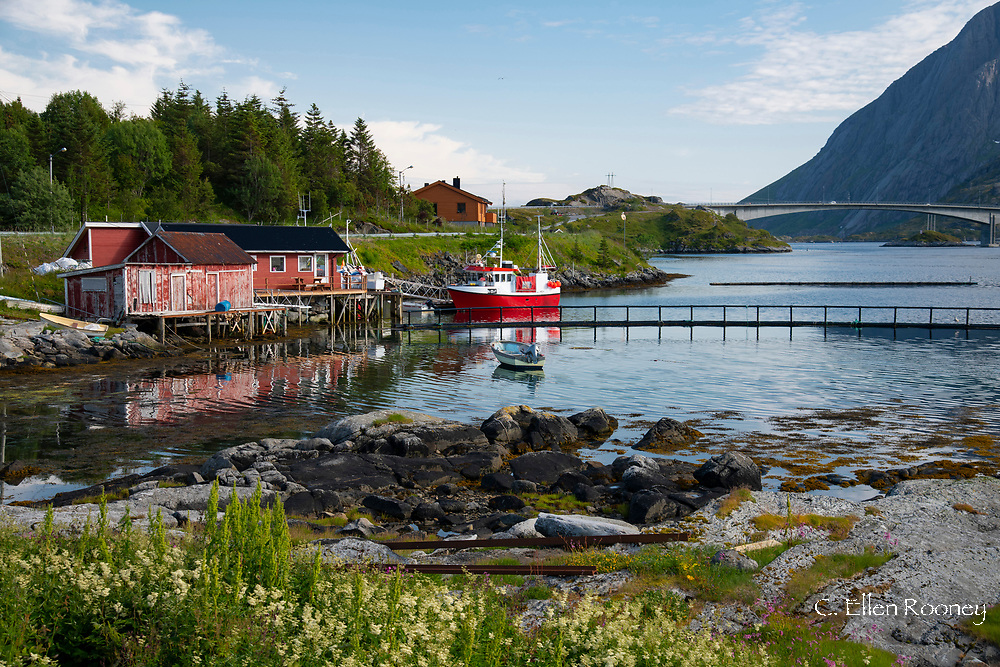 A fishing boat and dock houses near Kakern Bridge, Ramberg, Lofoten Islands, Norway
