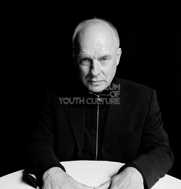 Man staring at camera with hands on table.