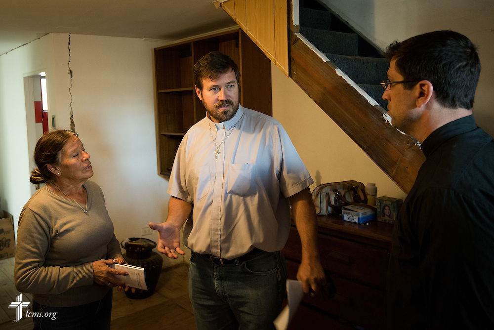 The Rev. Cristian E. Rautenberg, president of the Confessional Lutheran Church of Chile (center), translates to the Rev. Ross Johnson, director of LCMS Disaster Response, what happened to the home of an earthquake victim (left) on Wednesday, April 23, 2014, in Alto Hospicio, Chile. The home was damaged by a magnitude 8.2 earthquake on April 1, 2014, that struck approximately 95km northwest of Iquique. The earthquake condemned several thousand homes and severely damaged more than 10,000 others. LCMS Communications/Erik M. Lunsford