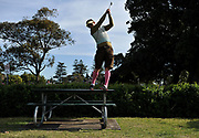 A golfer tees off from a park bench on World Urban Golf Day in Newcastle, Australia. Played with soft balls and without keeping score, Urban Golf is an attempt to take the game of golf away from the manicured lawns and into the urban environment.environment.