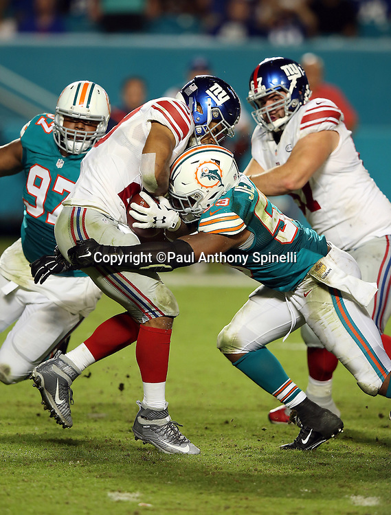 Miami Dolphins defensive tackle Jordan Phillips (97) chases New York Giants running back Rashad Jennings (23) as he gets tackled by Miami Dolphins outside linebacker Jelani Jenkins (53) in the third quarter during the NFL week 14 regular season football game against the Miami Dolphins on Monday, Dec. 14, 2015 in Miami Gardens, Fla. The Giants won the game 31-24. (©Paul Anthony Spinelli)