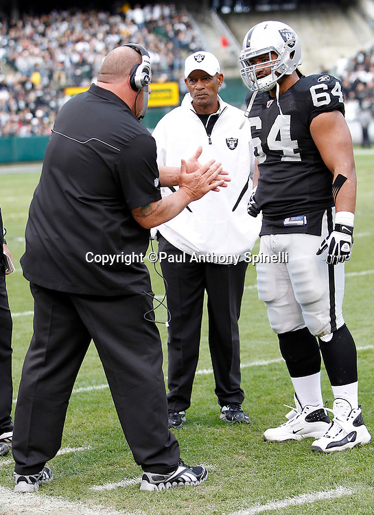 Oakland Raiders head coach Tom Cable talks to Oakland Raiders center Samson Satele (64) as director of squad development Willie Brown looks on during the NFL week 16 football game against the Indianapolis Colts on Sunday, December 26, 2010 in Oakland, California. The Colts won the game 31-26. (©Paul Anthony Spinelli)