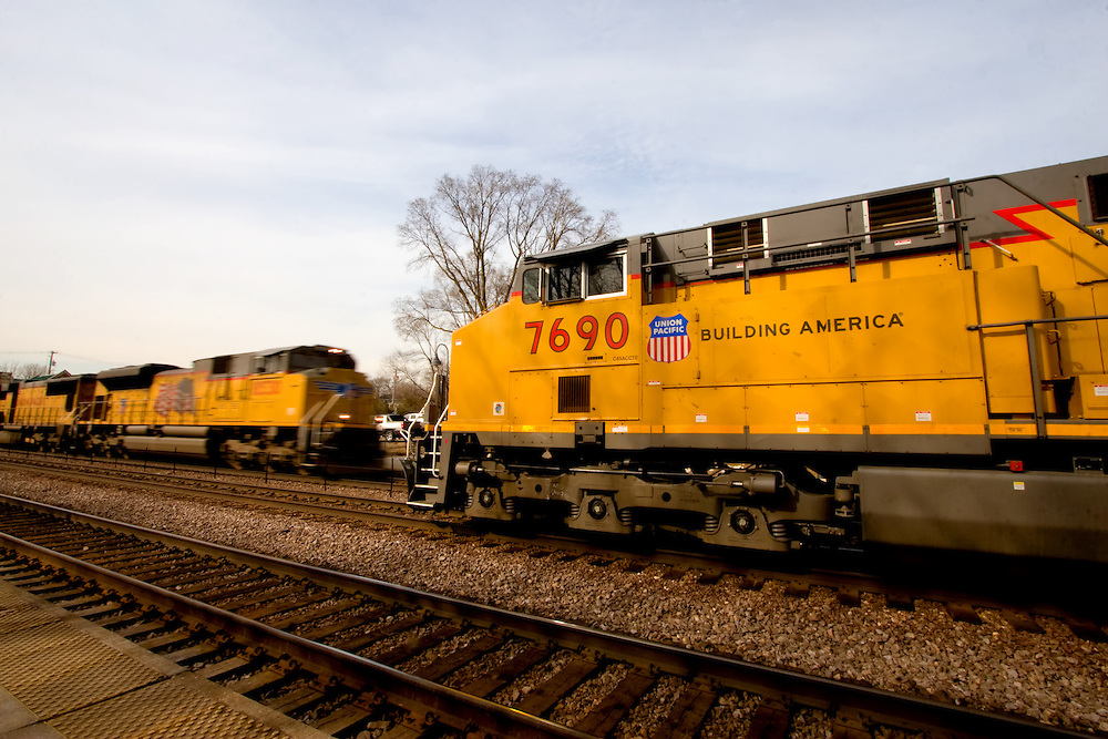 A fast moving Union Pacific intermodal train passes a stopped westbound train on the middle track at Winfield, IL.