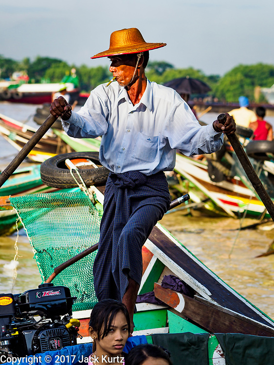 23 NOVEMBER 2017 - YANGON, MYANMAR: A boatman with a Burmese cheroot in his mouth brings his water taxi into the San Pya Fish Market Pier. San Pya Fish Market is one of the largest fish markets in Yangon. It's a 24 hour market, but busiest early in the morning. Most of the fish in the market is wild caught but aquaculture is expanding in Myanmar and more farmed fresh water fish is being sold now than in the past.    PHOTO BY JACK KURTZ