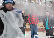 From right: Kristen Morris, Marty Ernsberger, and Abby Hidy look on as ice carver Jeff Petercsak, of Rock on Ice, carves a penguin in front of Baker University Center on Dec. 3, 2014. Photo by Lauren Pond